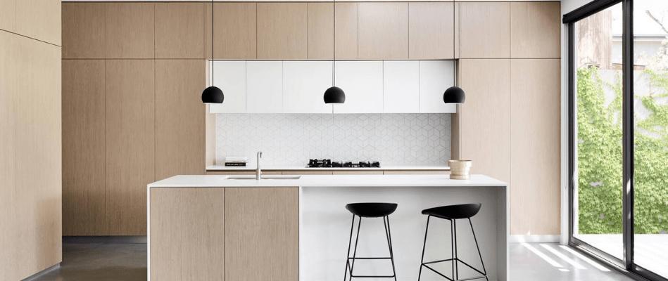 Cocina moderna con muebles de madera empotrados e isla con sillas y luminaria negra